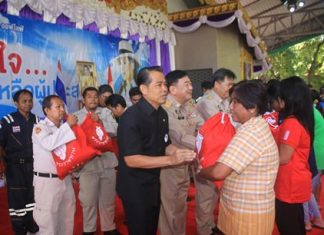 (L to R) Project Director Manus Nonuch, Chonburi Deputy Governor Phawat Lertmukda, and Banglamung District Chief Chakorn Kanjawattana help distribute 500 royal emergency bags to flood victims from HRH Princess Ubolratana.