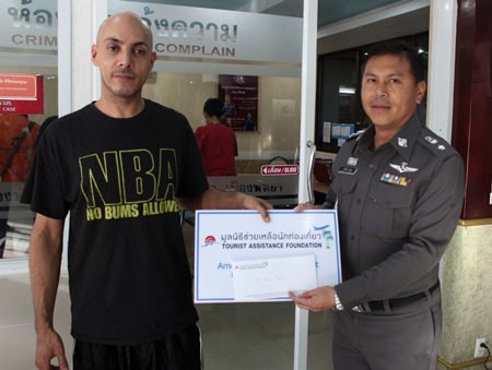 Briton Aser Ubus receives 6,000 baht from Kwanchanok Thana, representing the Tourist Assistance Foundation.