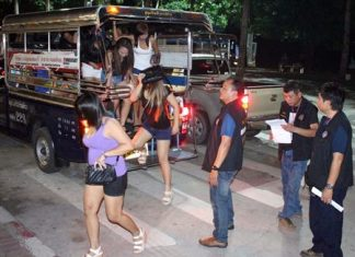 Alleged streetwalkers are transported en masse via baht bus to Pattaya police station.