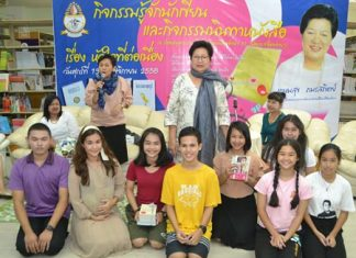 Kasemsuk 'Auntie Sai' Pamornsatit (standing center) read to Pattaya School No. 11 students in the school's library.