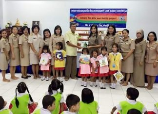 Members of the Rotary Club of Pattaya help stock the shelves of the Pattaya School No. 7 library with a donation of books.
