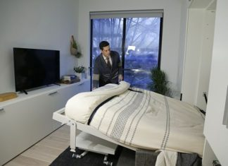 Stage 3 Properties co-founder Christopher Bledsoe demonstrates a retractable bed that turns into a sofa when stored inside one of the apartment units at the Carmel Place building in New York City. (AP Photo/Julie Jacobson)