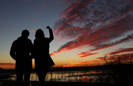 Kathleen O'Brien, of Portland, Maine, and Kathryn McBrady, of Scarborough, Maine, take in the view of a fiery winter sunset overlooking Back Cove, Thursday, Jan. 7, 2016, in Portland, Maine. Get ready for weather whiplash as powerful climatic forces elbow each other for starring roles in a weird winter show. (AP Photo/Robert F. Bukaty)