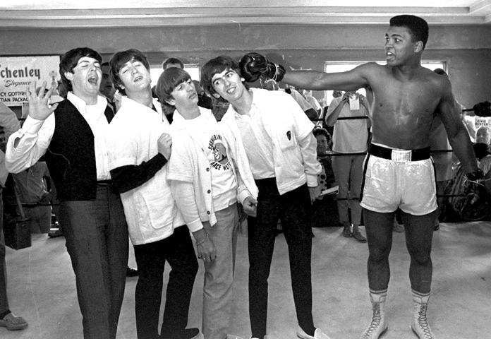 The Beatles (from left) Paul McCartney, John Lennon, Ringo Starr, and George Harrison, take a fake blow from Cassius Clay (Muhammad Ali) while visiting the heavyweight contender at his training camp in Miami Beach, Fla., Feb. 18, 1964. (AP Photo/File)
