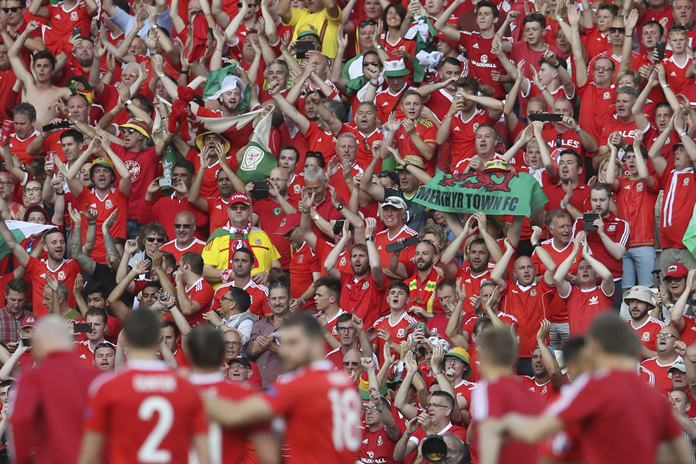 Wales fans cheers in front of the team after Wales won the Euro 2016 round of 16 soccer match between Wales and Northern Ireland, at the Parc des Princes stadium in Paris, Saturday, June 25, 2016. Wales beat Northern Ireland 1-0. (AP Photo/Petr David Josek)