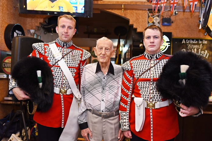 The oldest member of the Thailand branch of the Royal British Legion, 93 year old World War II veteran Archie Dunlop, is flanked by the Welsh guards.