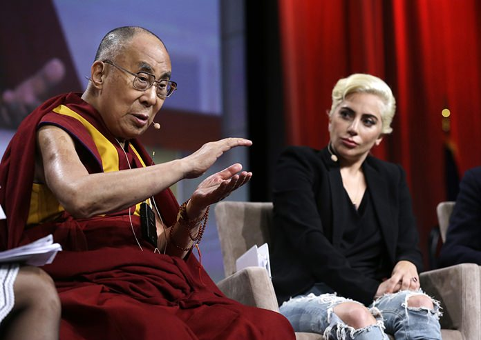 Lady Gaga listens as the Dalai Lama speaks during a question and answer session at the U.S. Conference of Mayors in Indianapolis, Sunday, June 26, 2016. (AP Photo/Michael Conroy)