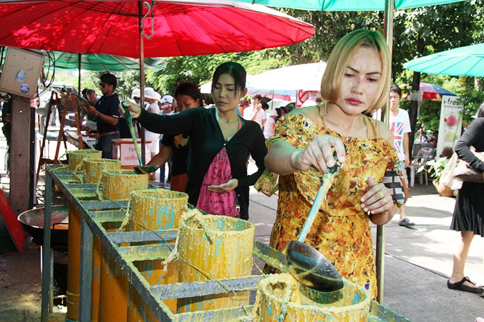 Devout Buddhists make merit by helping to make candles for the beginning of Buddhism's version of Lent.