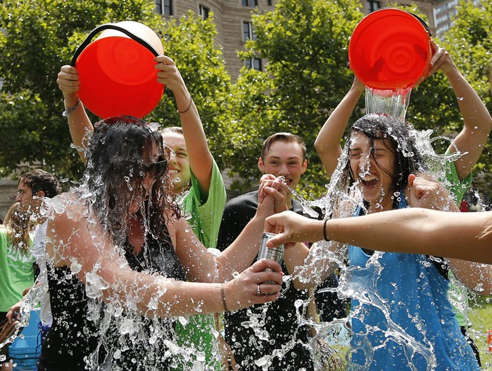 In this Aug. 7, 2014, file photo, two women get doused during the ice bucket challenge at Boston's Copley Square to raise funds and awareness for ALS. The ALS Association says money raised through the challenge helped fund a project that has discovered a gene linked to the disease. (AP Photo/Elise Amendola, File)