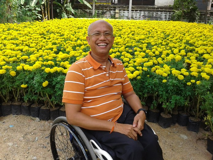 School executive Manop Eimsa-ard presides over the opening of a market selling flowers planted by disabled students for Mother's Day.