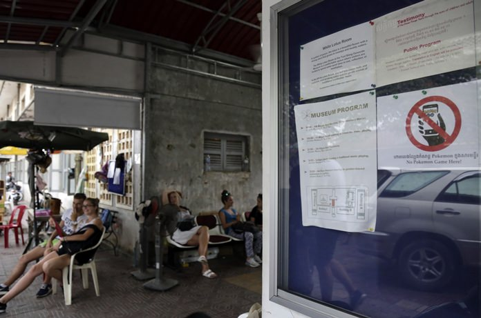 """A warning sign, right, reading """"No Pokemon Game"""" is stuck at a front gate of Tuol Sleng genocide museum, in Phnom Penh, Cambodia, Wednesday, Aug. 10. (AP Photo/Heng Sinith)"""