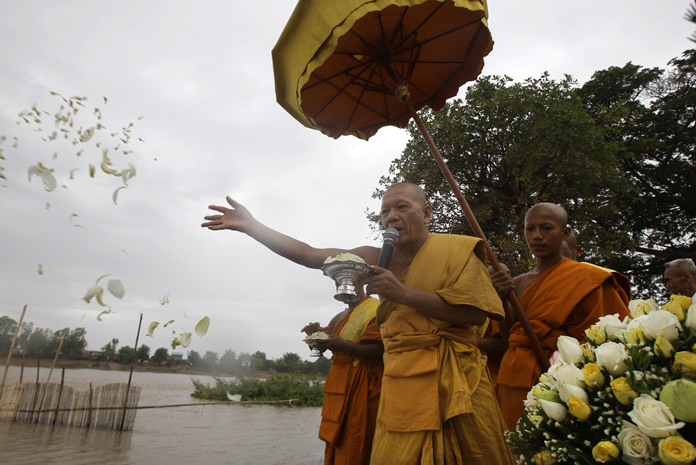 A monk casts flowers onto the Tonle Sap river during a Buddhist ceremony as locals search for missing Buddha statues at Kean Kleang village, Kampong Chhnang province, northwest of Phnom Penh, Cambodia, Thursday, Aug. 18. (AP Photo/Heng Sinith)