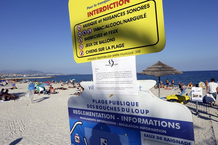 A bylaw forbidding women to wear burkini is posted on an information panel at a public beach in Villeneuve-Loubet, French Riviera, southern France, Friday, Aug. 26. France's top administrative court has overturned Villeneuve-Loubet's burkini ban after some Muslim women were ordered to remove body-concealing garments on French Riviera beaches. (AP Photo/Claude Paris)