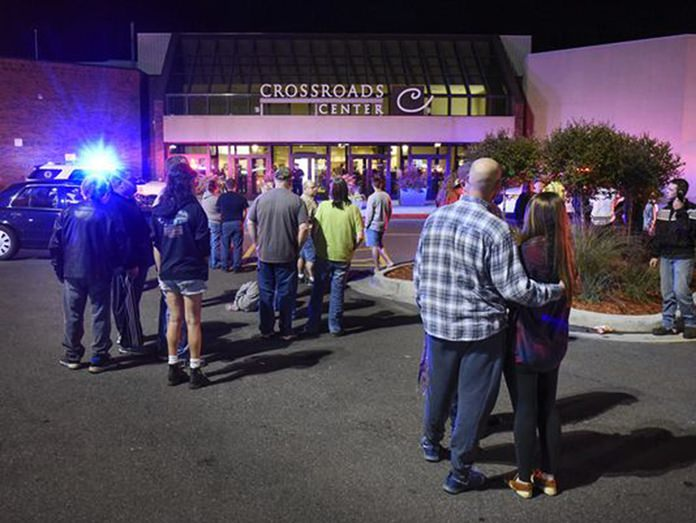 People stand near the entrance of Crossroads Center shopping mall in St. Cloud, Minn., as officials investigate a reported multiple stabbing incident, Saturday, Sept. 17. (Dave Schwarz/St. Cloud Times via AP)