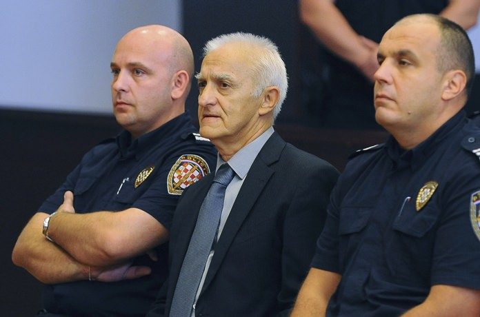 Dragan Vasiljkovic, center, a former Serb military commander sits between guards in a courtroom at the beginning of his trial in Split, Croatia, Tuesday, Sept. 20. (AP Photo)