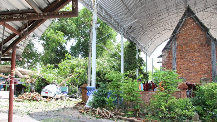 A giant Bodhi tree fell on top of a house and car (left) but didn't damage an ancient shrine (right) built in the late Ayutthaya period.