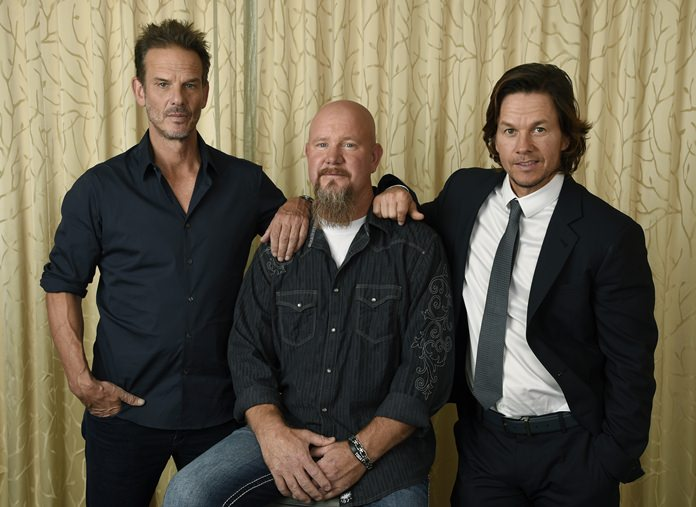 """Mike Williams (center) an electrician and survivor on the Deepwater Horizon oil rig, poses with Peter Berg (left) director of the film """"Deepwater Horizon,"""" and cast member Mark Wahlberg at the Ritz-Carlton Hotel in Toronto. (Photo by Chris Pizzello/Invision/AP)"""
