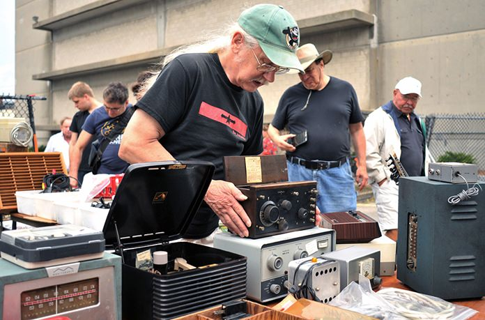 Vendor Chuck Ochs shows a 1921 Crosley Model 51 radio, priced at $100, at MIT's Radio Society flea market. (AP Photo/Collin Binkley)