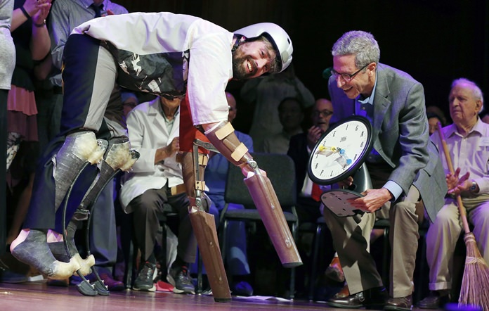 Thomas Thwaites (left) accepts the Ig Nobel prize in biology for creating prosthetic extensions of his limbs that allowed him to move like and roam in the company of goats. (AP Photo/Michael Dwyer)