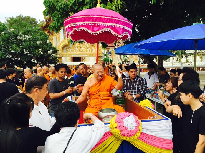 The abbot at Wat Chaimongkol blesses the congregation with holy water.