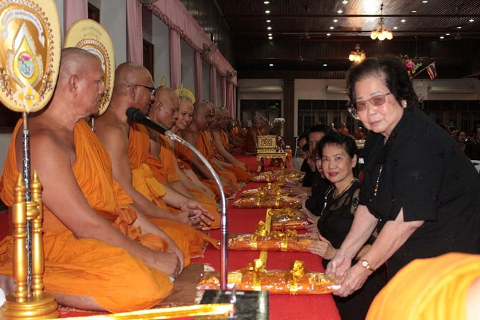 Devout Buddhists present robes to monks at Wat Chaimongkol for Tak Bat Devo.