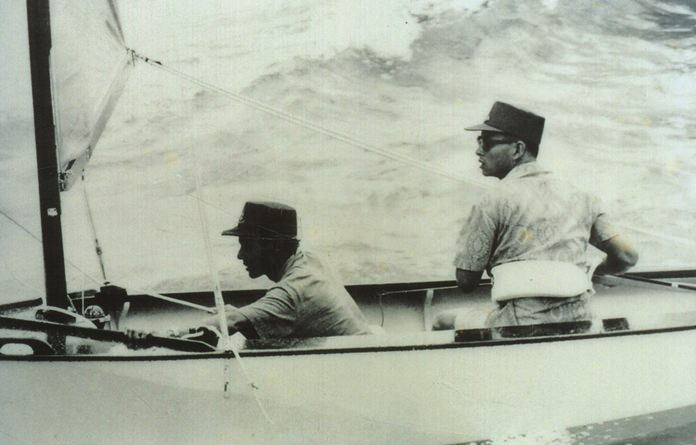 "HM the King learning to sail, with his ""tutor"" HSH Prince Bhisadej."