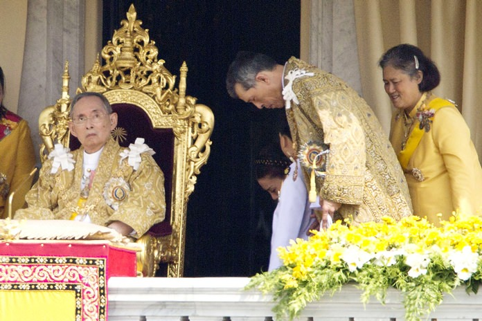 In this Dec. 5, 2012, file photo, His Majesty King Bhumibol Adulyadej, left, is seated as Crown Prince Vajiralongkorn, second left, and Princess Sirindhorn, right, stand after he addressed the crowd from a balcony of the Ananta Samakhom Throne Hall on his 85th birthday in Bangkok. (AP Photo/Wason Wanichakorn, File)