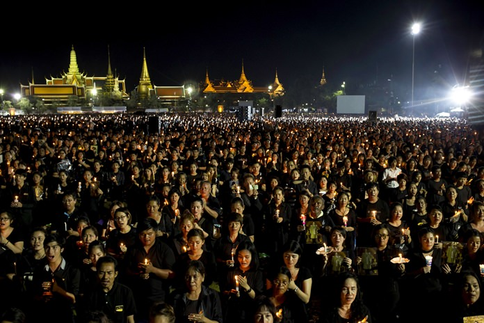 Mourners hold candles and sing Thailand's Royal Anthem on the evening of Saturday, Oct. 22, 2016. (AP Photo/Wason Wanichakorn)