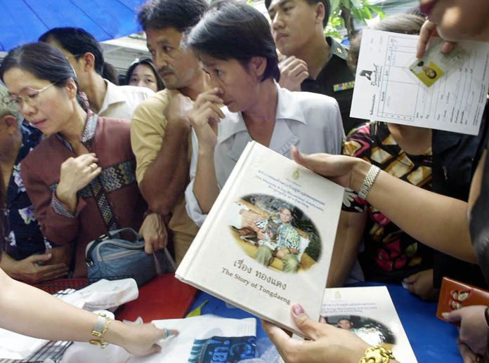 "People queue up to buy a copy of ""The Story of Thongdaeng,"" written by His Majesty King Bhumibol Adulyadej about a stray dog he adopted. (AP Photo/Apichart Weerawong)"
