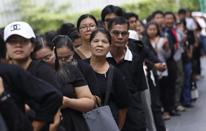 Mourners line up to buy commemorative banknotes in Bangkok.(AP Photo/Sakchai Lalit)