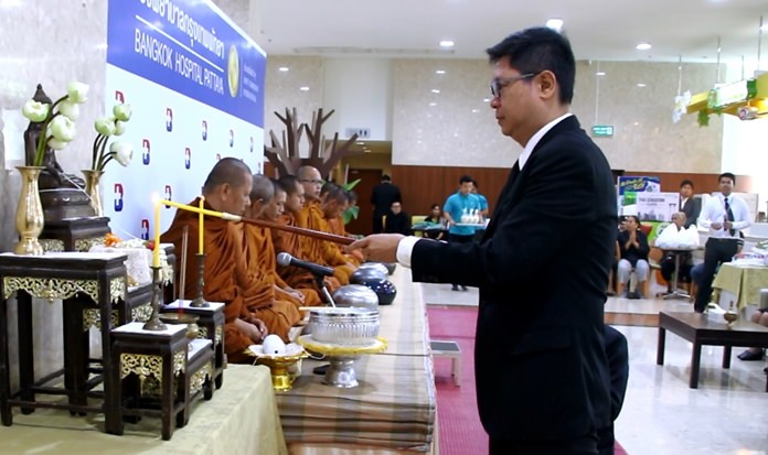 "Director Pichit Kangwolkit leads the lighting of candles and incense in the ""ratanattaya"" worship service at Bangkok Hospital Pattaya."