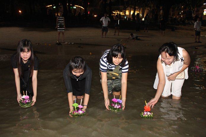 Families float their krathongs together along Pattaya Beach.