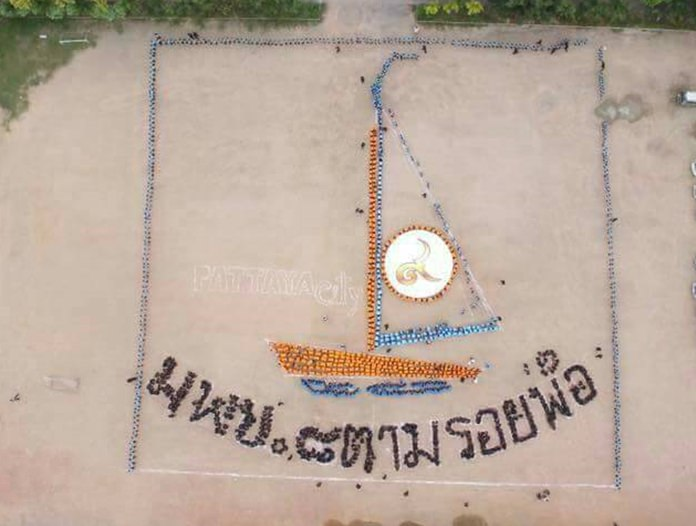 Students of Pattaya School 8 form an image of a sail boat and a message to HM the late King in heaven saying that 'We will follow the footsteps of our Father'.