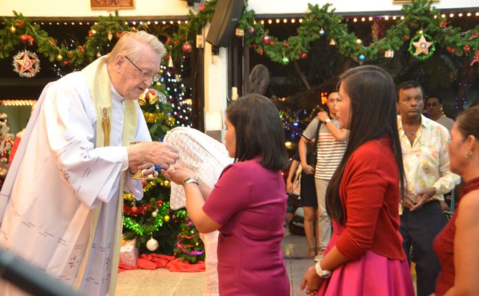 Worshippers receive the Eucharist during Christmas Mass at St. Nikolaus Church.