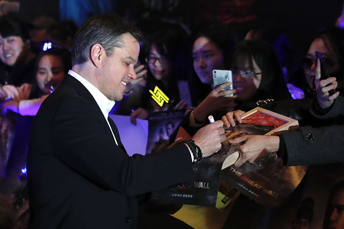 """Actor Matt Damon signs autographs for Chinese fans as he arrives at a red carpet event for the movie """"The Great Wall"""" at a hotel in Beijing, Tuesday, Dec. 6. (AP Photo/Andy Wong)"""