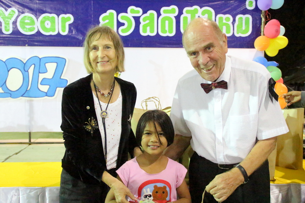 Dr. Margret and Dr. Otmar Deter give a gift to a little girl.