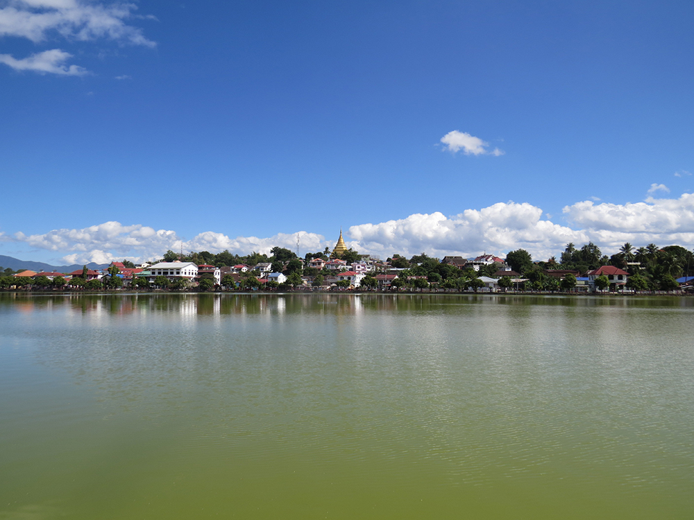 The scenic Naung Tong Lake in Kengtung, Myanmar is capped by the golden glow of Wat Jom Kai.