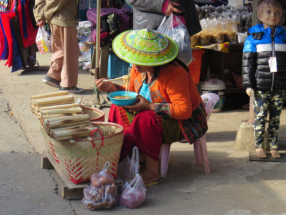 A local vendor enjoys some noodles while waiting for customers. The hats are handmade and embroidered during the rainy season.