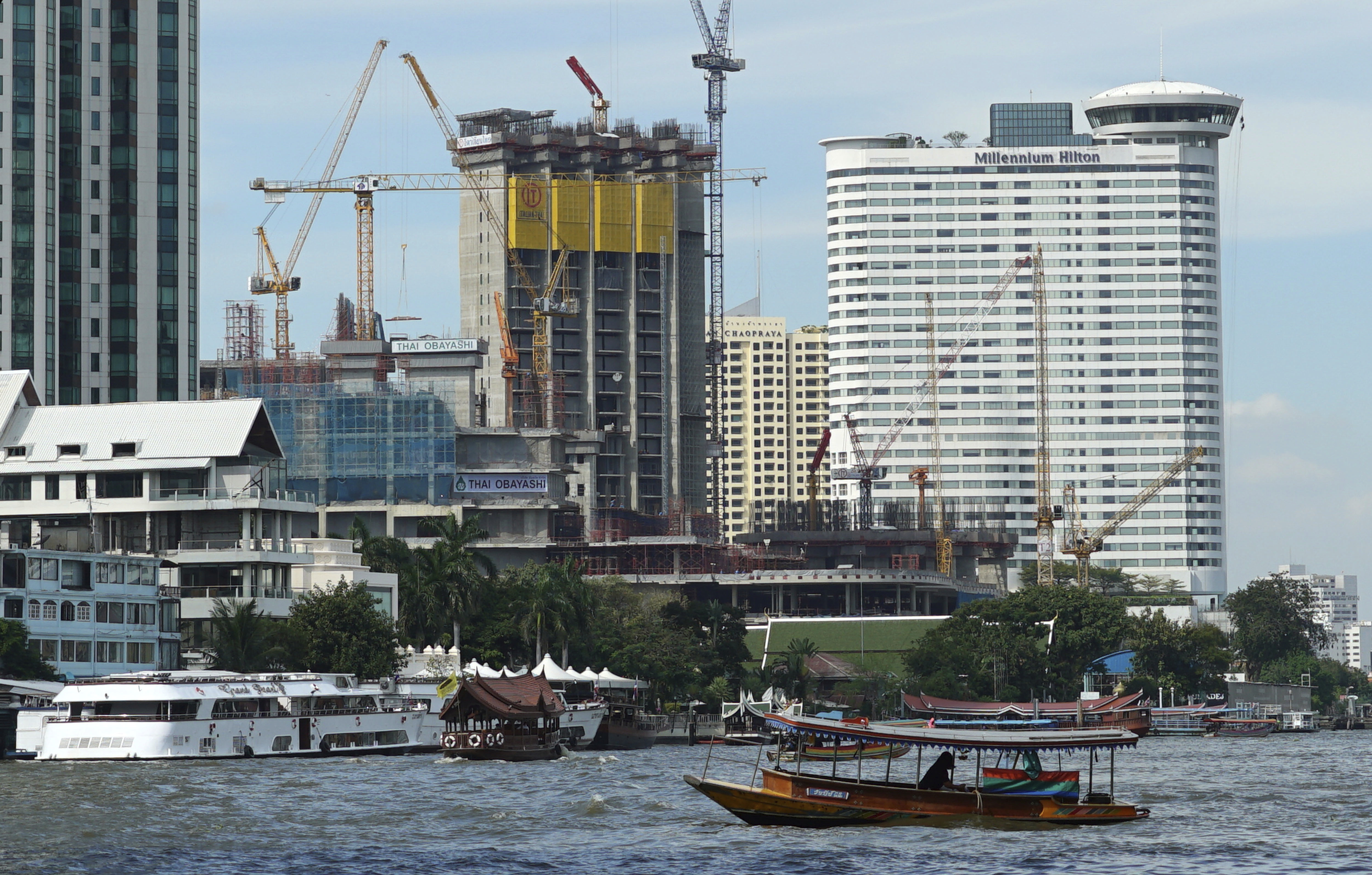 A riverboat taxi crosses the Chao Phraya River in front of massive construction projects Wednesday, Jan. 18, 2017, in Bangkok. A United Nations report says Asia's economic outlook for 2017 is strong despite slowing global growth due to sluggish international trade and investment. (AP Photo/Dake Kang)