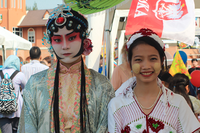 An Ancient Chinese Opera performer greets a young lass from Myanmar.