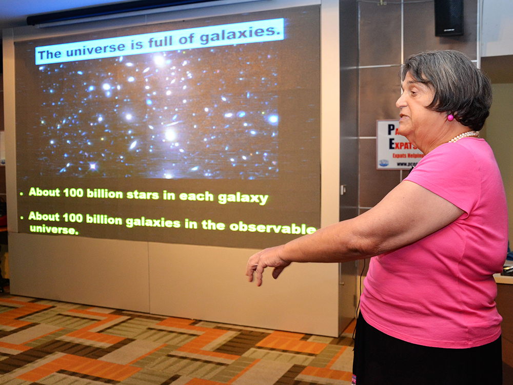 Alicia Beaudin explains to her PCEC audience that Cosmology includes our universe, which is full of galaxies. She points out that there are about 100 billion stars in each galaxy and 100 billion galaxies in the observable universe.