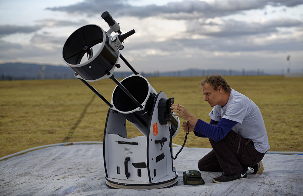 Astronomer and company co-founder Daniel Chu Owen sets up a telescope during a visit by The Traveling Telescope. (AP Photo/Ben Curtis)