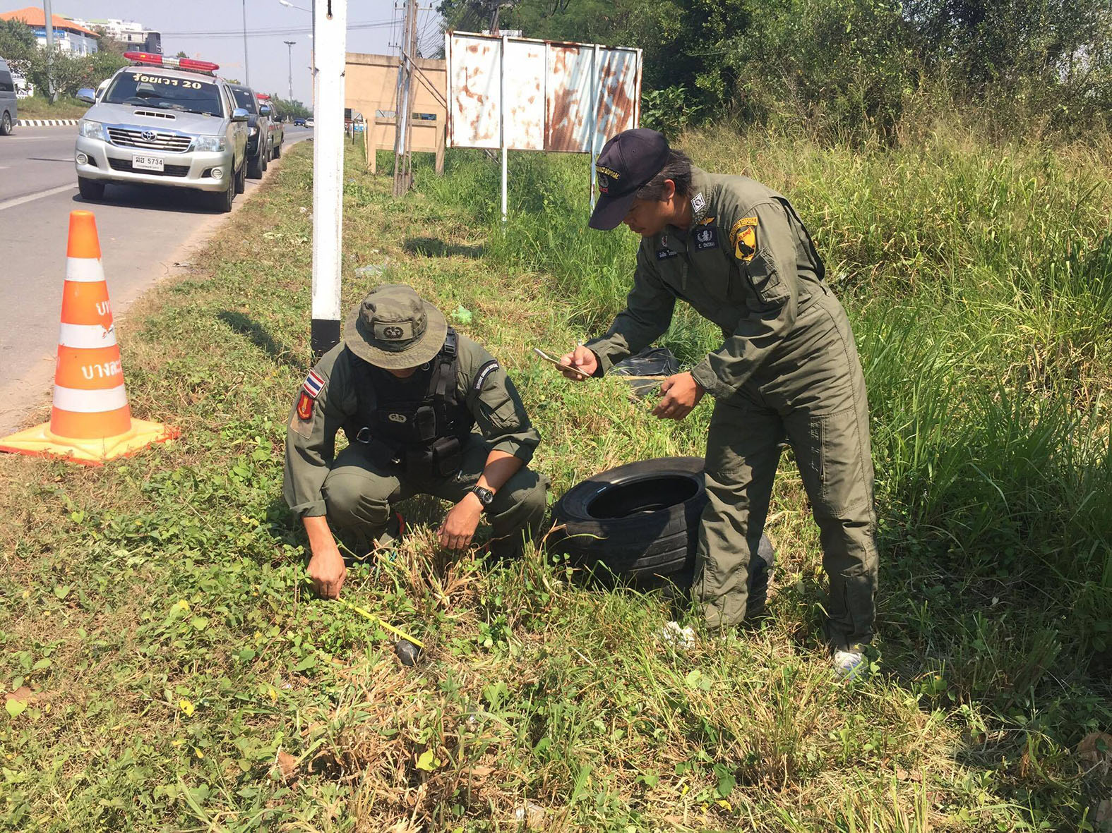 Bomb squad police begin the process of defusing an IED found on a Sattahip roadside.