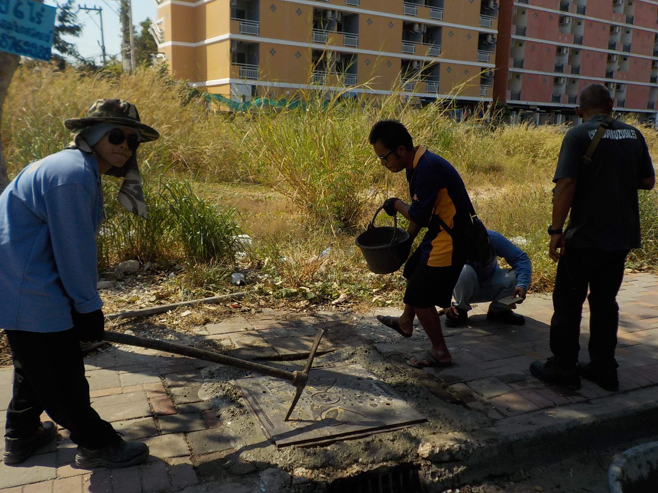 Pattaya city workers repair drainage covers posing a hazard to pedestrians near Bali Hai Pier.
