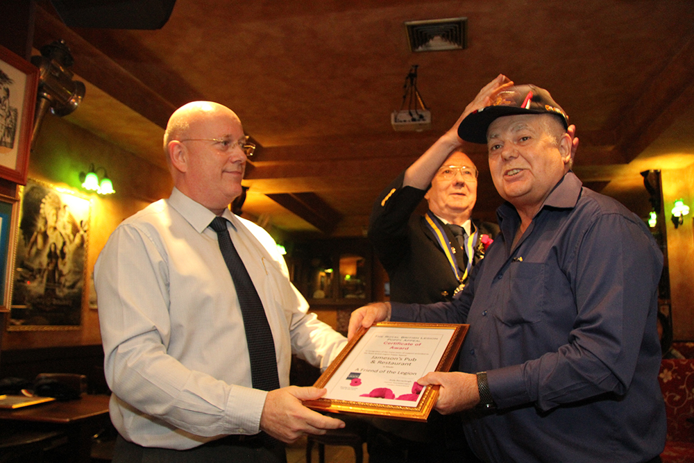 Graham Macdonald (left), President of the Royal British Legion Thailand presents Kim Fletcher (right) with a 'Friend of the Legion' Award, in recognition of the many years of outstanding support to the Royal British Legion Poppy Appeal in Thailand.