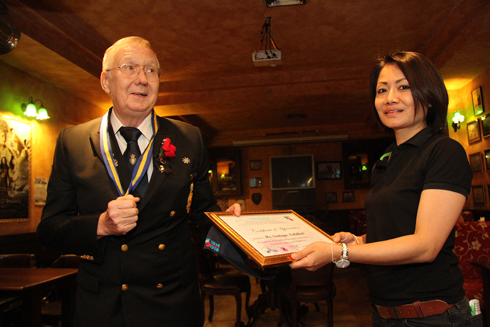 Andy Barraclough, Chairman of the Royal British Legion, Thailand (left) presents Sontaya Nalidlad a certificate of appreciation for being the staff member who contributed the most time, energy and effort to the annual Royal British Legion Poppy Appeal activities which take place at Jameson's.