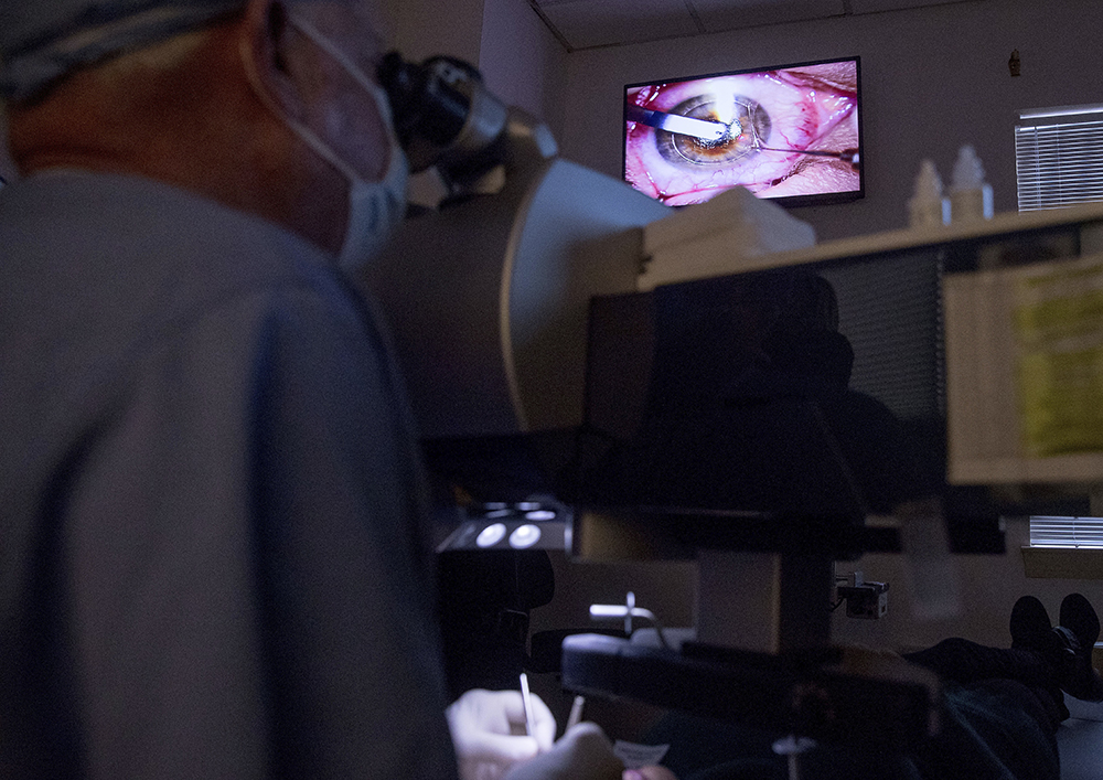 In this photo taken Feb. 1, 2017, a live video feed is displayed on a screen above Dr. Mark Whitten, left, as he performs a short eye surgery procedure on patient Christianne Krupinsky in Washington, to insert a Raindrop inlay, a disc implanted in the cornea to reshape it for better close-up focus. This new kind of eye implant corrects presbyopia, the need for reading glasses that eventually hits all of us, usually starting in the 40s. (AP Photo/Andrew Harnik)