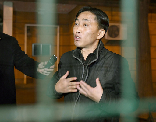 North Korean Ri Jong Chol speaks to reporters from behind a fence at the North Korean Embassy in Beijing early Saturday, March 4, 2017.(Naohiko Hatta/Kyodo News via AP)