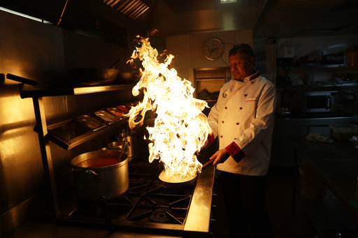 Chef Mohammed- Faizul Haque uses lemon juice to make flames as he demonstrates how to give a smokey flavour to dishes such as Kuchi Chilli Chicken at the Taste of India curry restaurant in London, Thursday, March 9, 2017. (AP Photo/Matt Dunham)