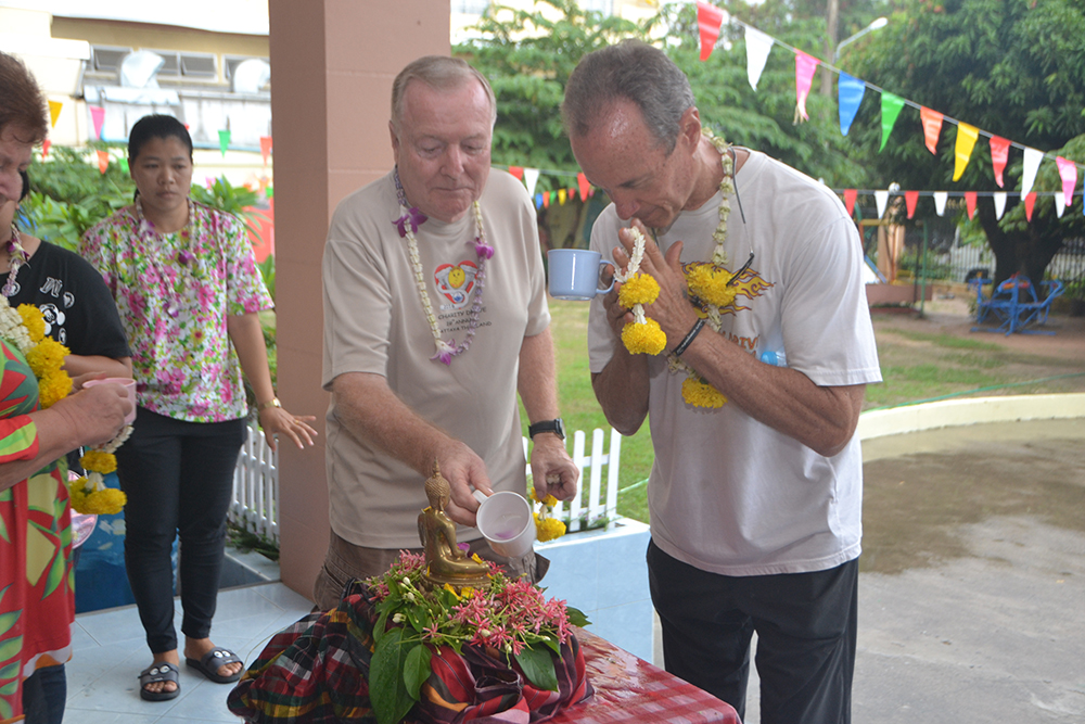 Lewis Underwood and Erle Kershaw from Jesters Care for Kids pour fragrant water on the Buddha statue as part of the bathing the Buddha image ritual during the Fountain of Life's Songkran celebration.